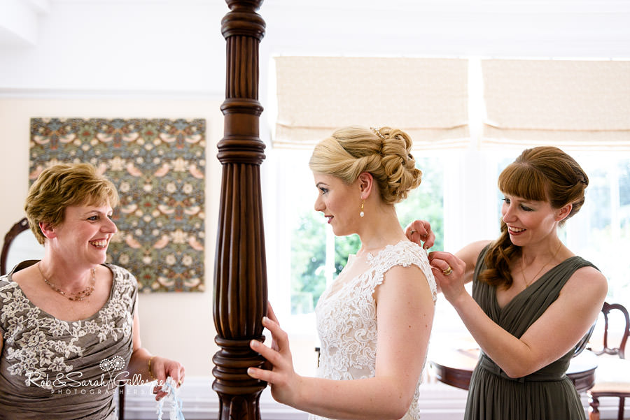 Bridesmaid helping fasten dress while bride chats to mother