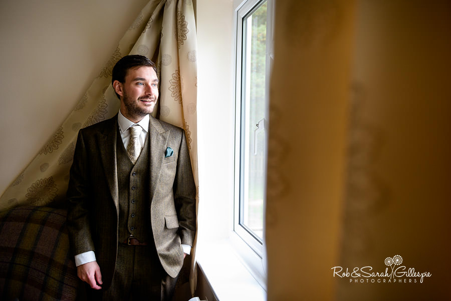 Portrait of groom in window