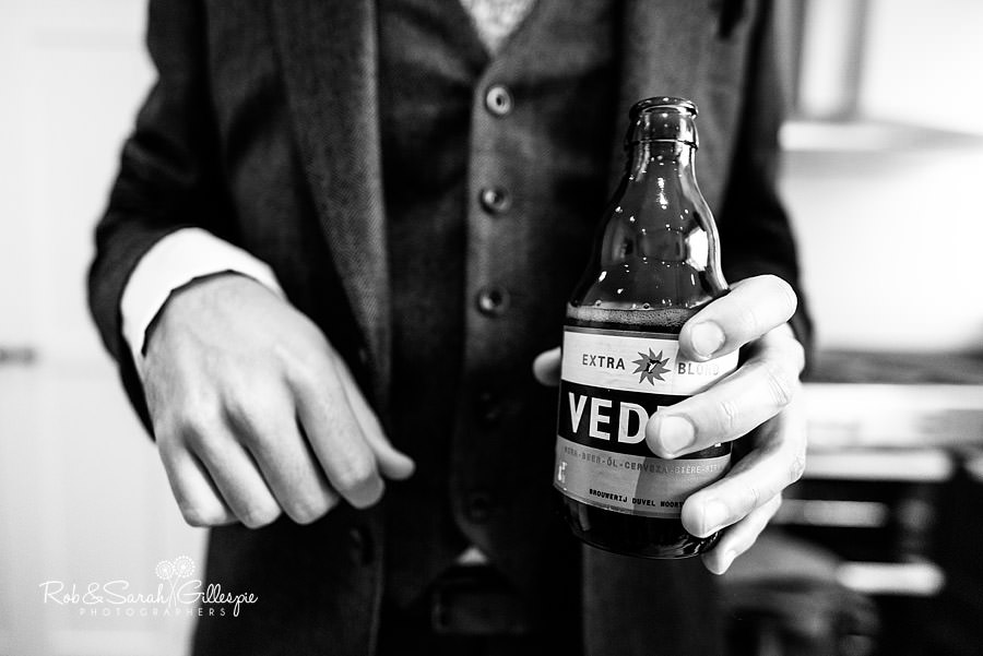 Close-up photo of groom olding bottle of beer before wedding