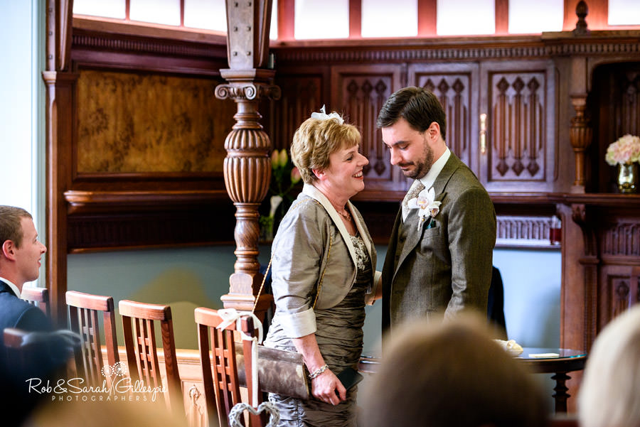 Groom's mother talks to son before wedding service starts