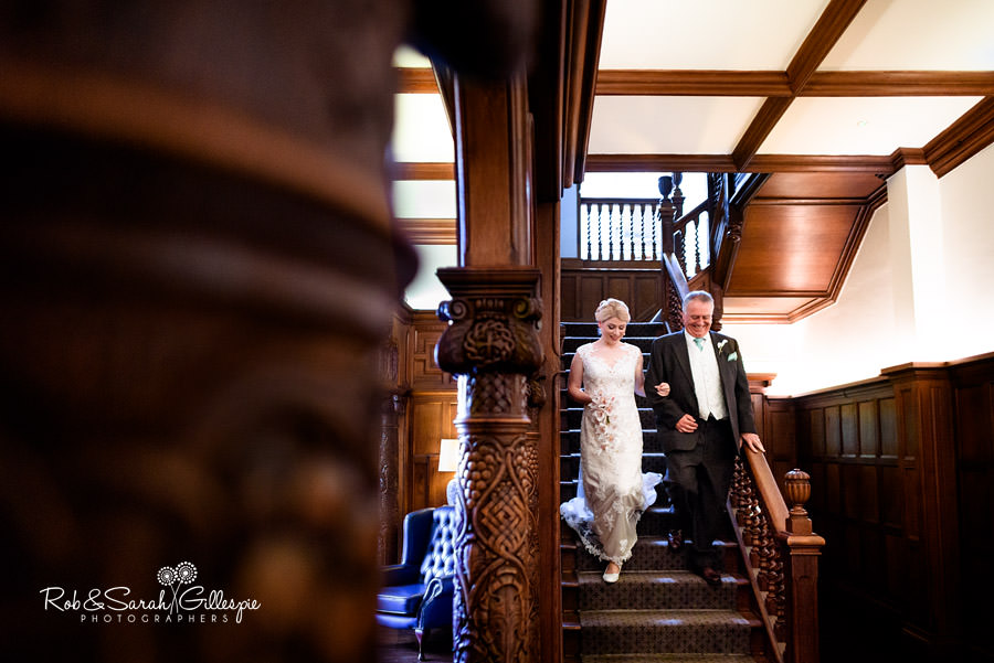 Bride and father walk down stairway at Pendrell Hall, ready for wedding service