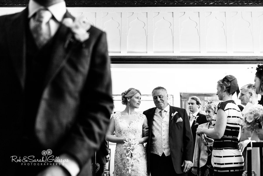 Bride and father walk up aise towards camera in Morning Room at Pendrell Hall