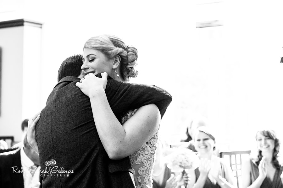Bride and groom share emotional hug at end of wedding service