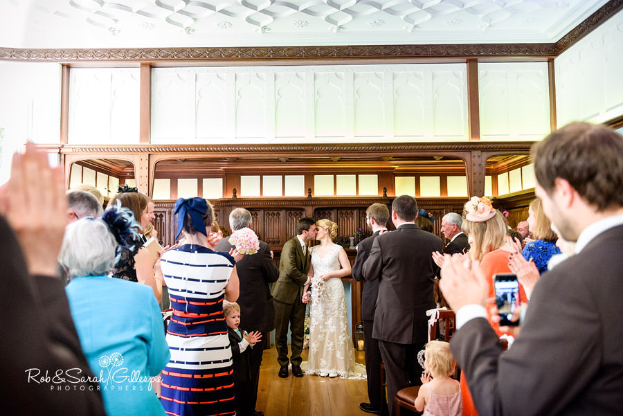 Bride and groom kiss while guests clap