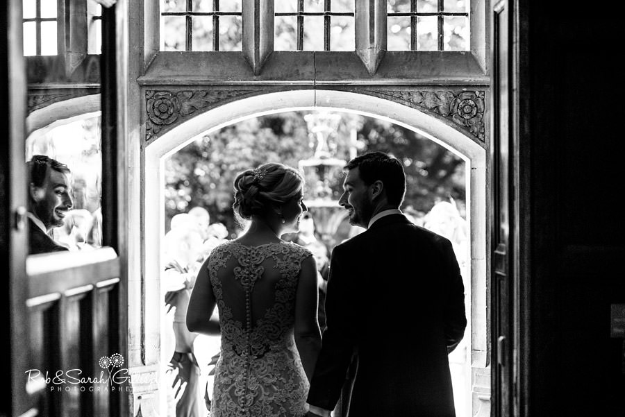 Black and white photo of bride and groom exiting Pendrell Hall after wedding service
