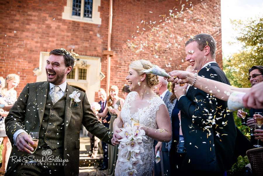 Bride and groom have confetti thrown by guests outside Pendrell Hall