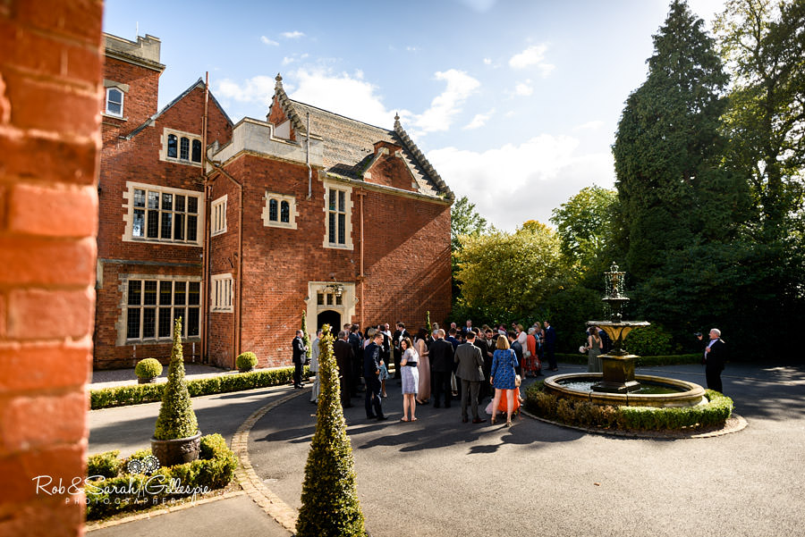 Wide-angle photo of Pendrell Hall as wedding guests mix after wedding
