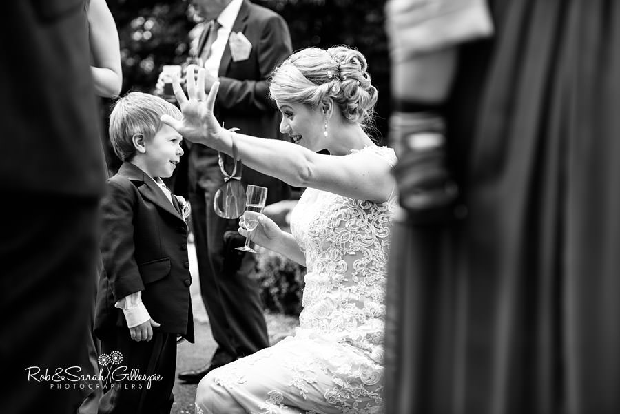 Low-angle picture shooting through guests as bride hugs pageboy