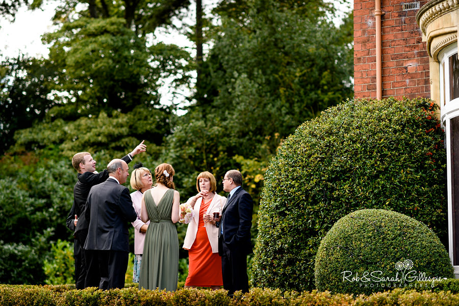 Wedding guests chat in Pendrell Hall gardens during drinks reception