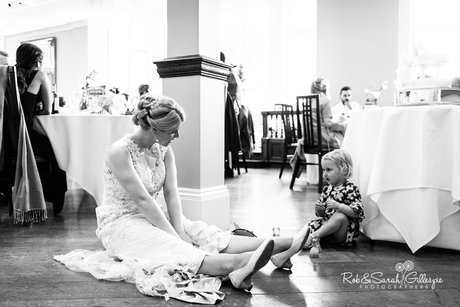 Bride sits on floor and talks to young girl during wedding breakfast at Pendrell Hall