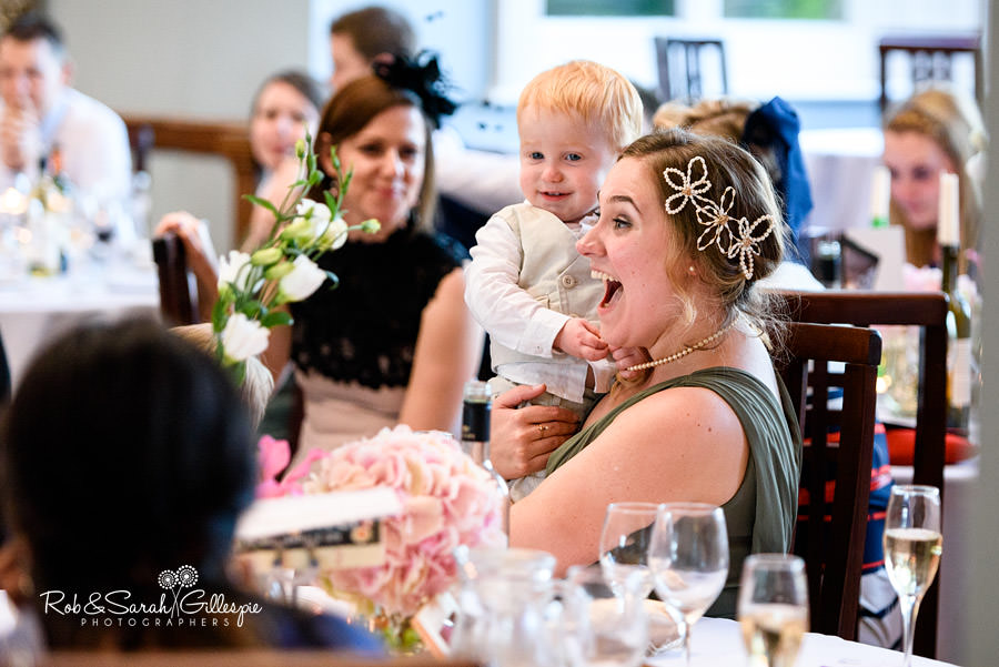 Bridesmaid holds up pageboy during wedding speeches