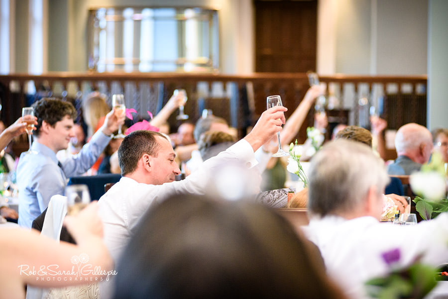 Wedding guests raise glasses during speeches