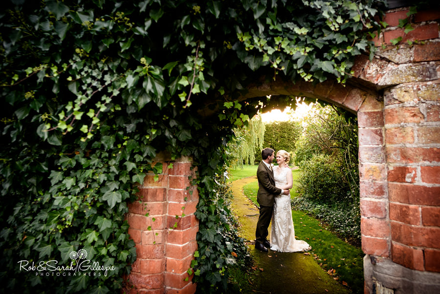 View through old brick archway at Pendrell Hall at bride and groom
