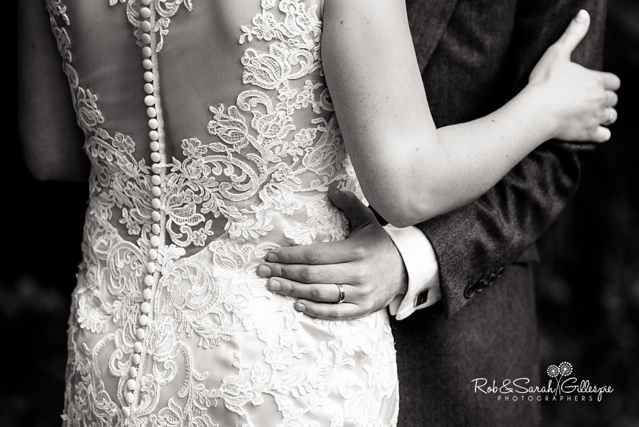 Close-up photo of bride and groom embracing, showing off beautiful detail of dress