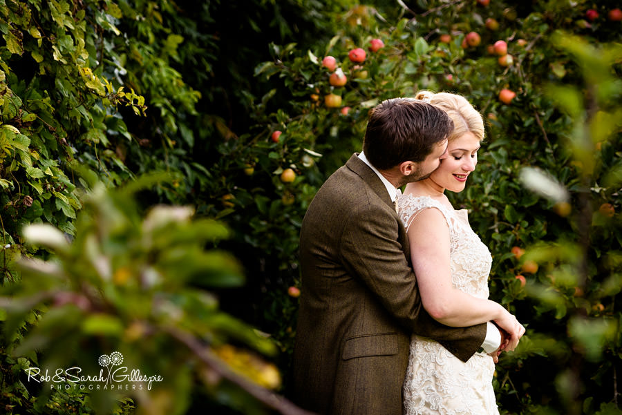 Groom kisses his bride on the cheek in gardens at Penrell Hall