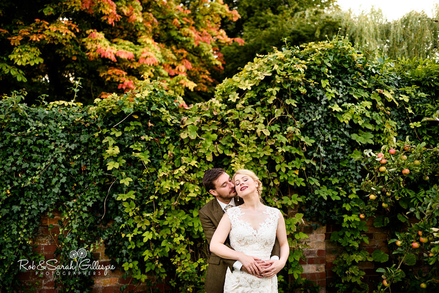 Bride and groom together in front of ivy-covered wall with Autumn colours on trees behind