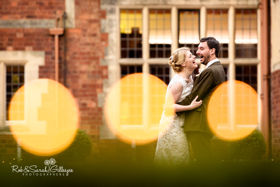 Bride and groom laughing hysterically at Pendrell Hall with round lights in foreground
