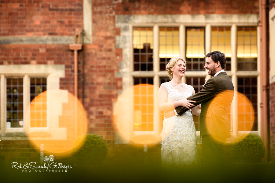 Newlyweds laughing at Pendrell Hall with round lights in foreground