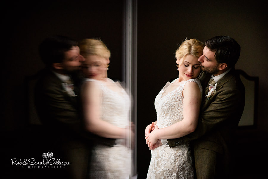 Bride and groom snuggle in beautiful window light with reflection