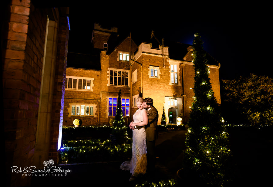 Bride and groom together in front of Pendrell Hall at night
