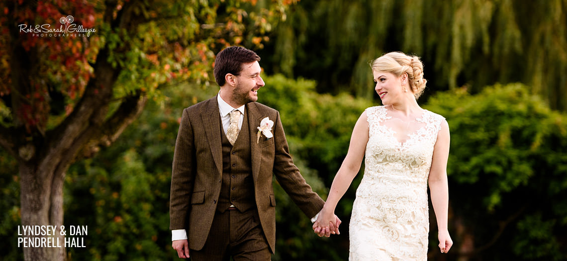 Newly married couple walk hand-in-hand at Pendrell Hall