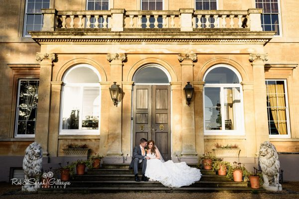 Bride and groom sitting on steps at Spring Grove House in beautifule vening light