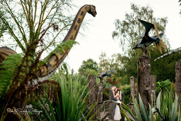 Bride and groom in dinosaur park at Spring Grove House