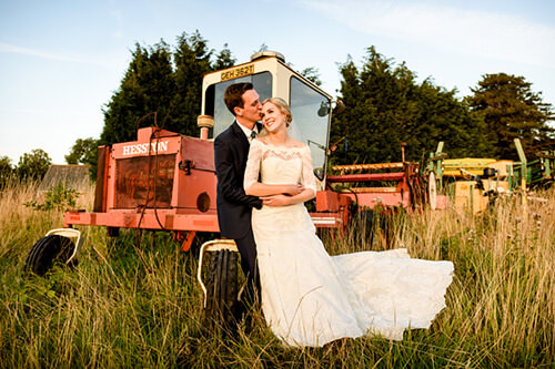 Bride and groom relaxing together in front of old tractor at Wishaw Country Sports wedding