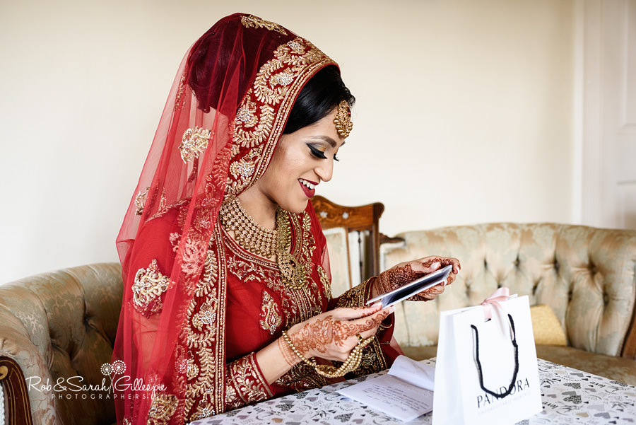 Bride in red headscarf opening presents from groom