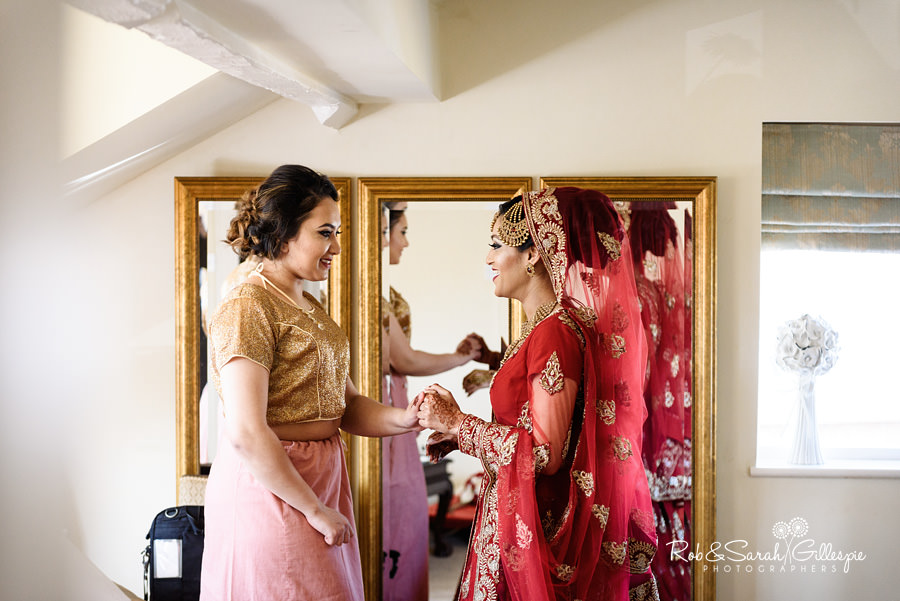 Bride and bridesmaid talking before wedding at Warwick House