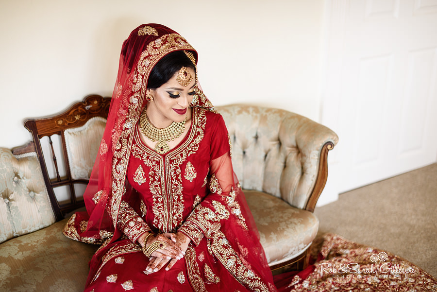Portrait of bride seated, wearing Indian wedding dress in red and gold