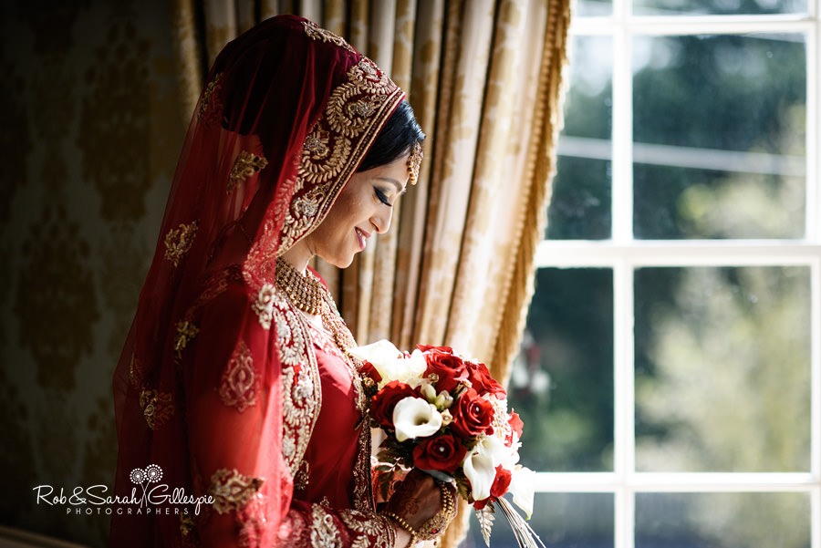 Bride looking at her flowers in window at Warwick House