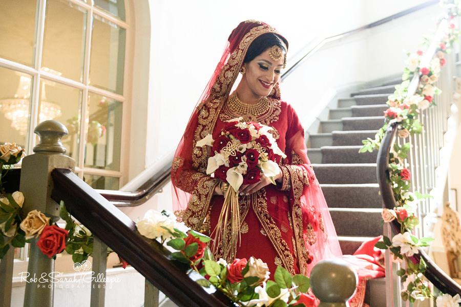 Bride walks down stairway at Warwick House smiling before wedding ceremony