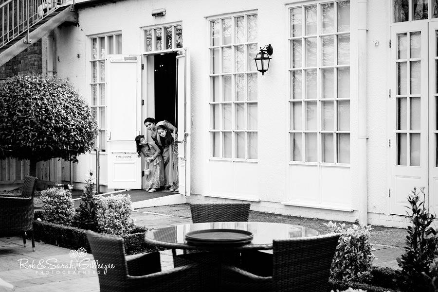 Flower girls and bridesmaid peek around door before start of outdoor wedding service
