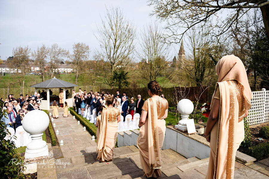 Flower girls and bridesmaids start their walk up the aisle at Warwick House