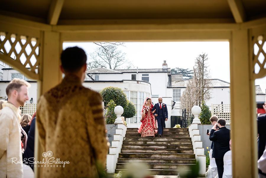 Bride desceneds steps during Warwick House outdoor wedding ceremony