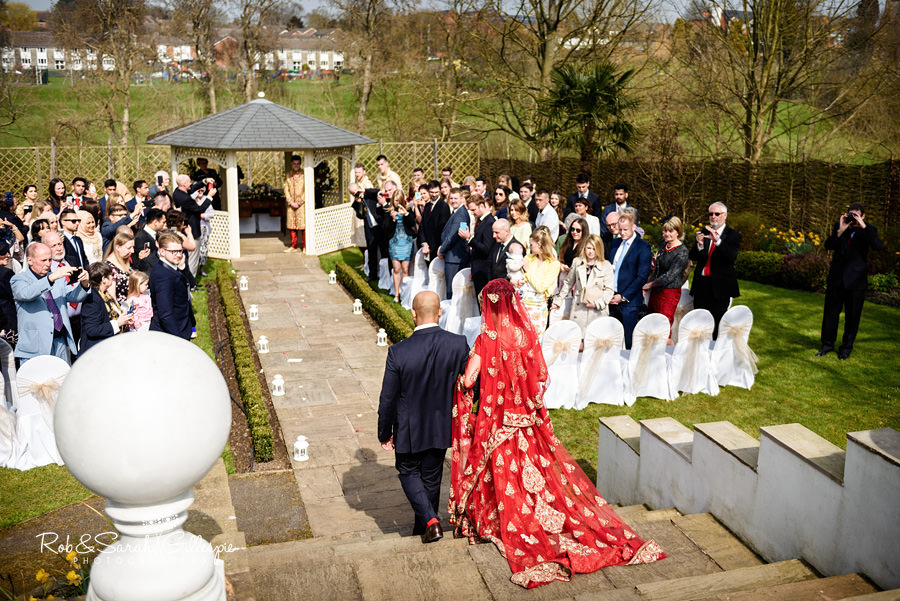 Bride desceneds steps during Warwick House outdoor wedding ceremony