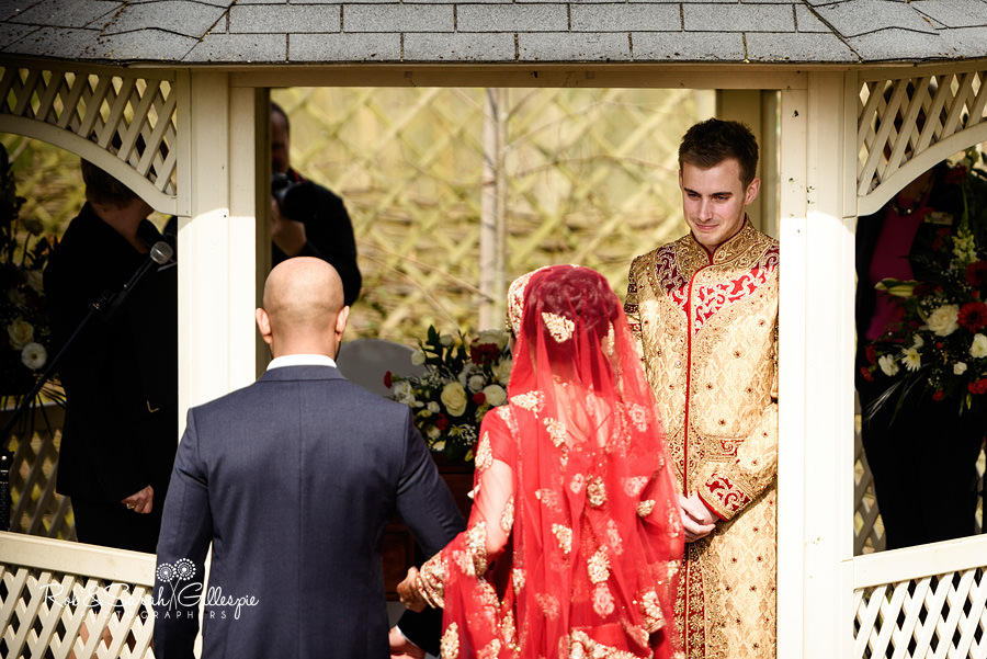 Groom looks at his bride during outdoor wedding service at Warwick House