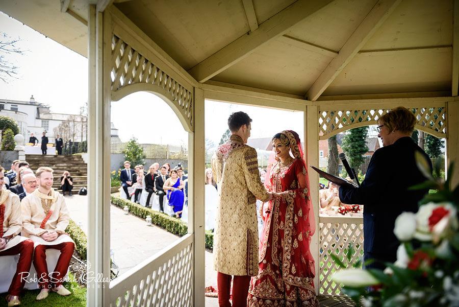 Bride and groom start outdoor wedding ceremony in Warwick House gardens