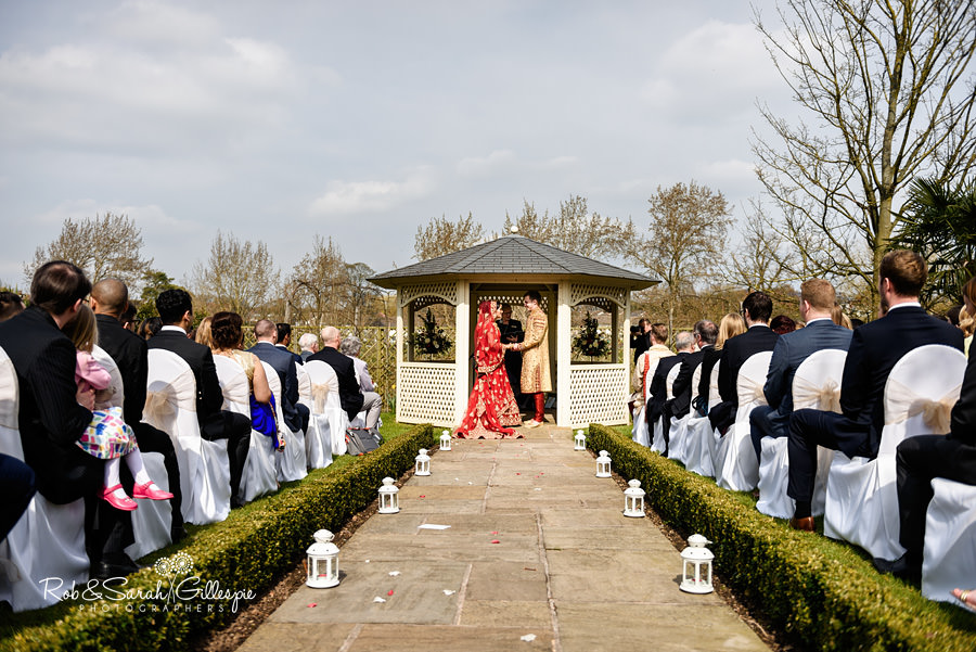Bride and groom start outdoor wedding ceremony in Warwick House gardens