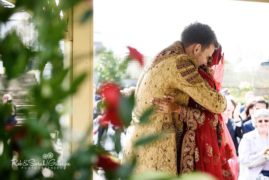 Bride and groom hug during wedding service at Warwick House outdoor ceremony