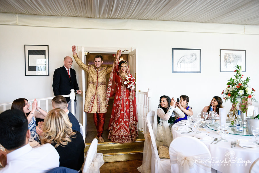 Bride and groom make their entrance for wedding breakfast in Warwick House