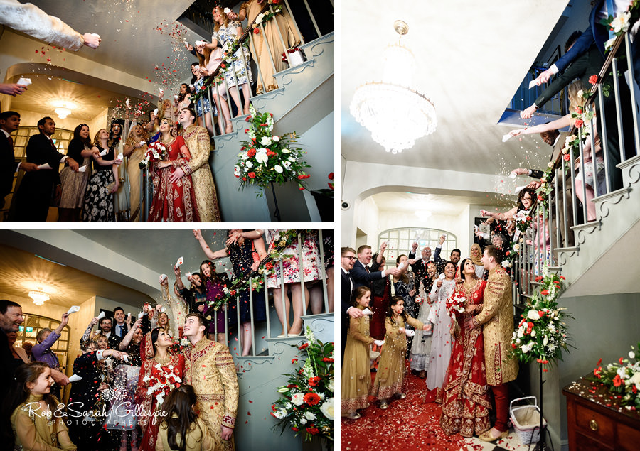 Confetti thrown over bride and groom inside Warwick House hallway