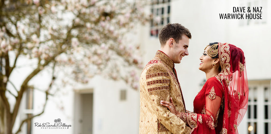 Bride and groom in traditional Indian wedding clothes outside Warwick House in Southam