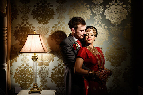 Bride and groom in suit and sari in beautiful light in Warwick House honeymoon suite