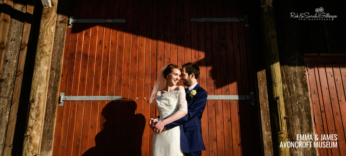 Bride and groom in front of barn doors at Avoncroft Museum