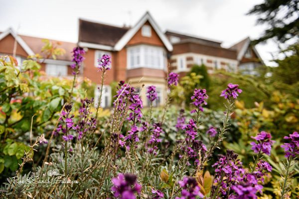 Front view of Nuthurst Grange with beautiful purple flowers