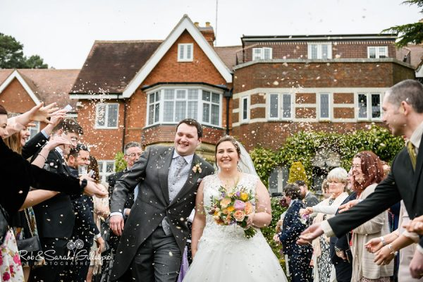 Bride and groom walk through confetti thow at Nuthurst Grange venue