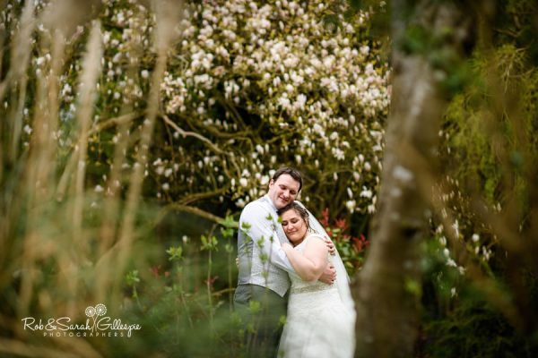 Bride and groom embrace in grounds at Nuthurst Grange