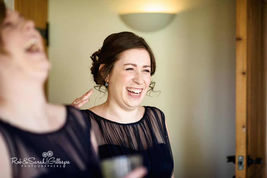 Bridesmaids laugh with bride while preparing for wedding